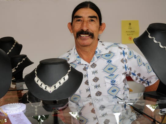 Precious metals artist Juan Lopez stands next to some