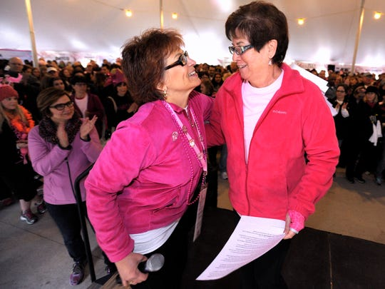 Dr. Pamela Benitez, left, 60, of Bloomfield Hills, co-founder of Shades of Pink and breast-cancer surgeon at Beaumont Hospital in Royal Oak, hugs Michigan's First Lady and 11-year breast-cancer survivor Sue Snyder on the stage before the walk.