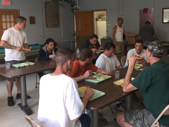 Men eat a meal at Hope House earlier this year.