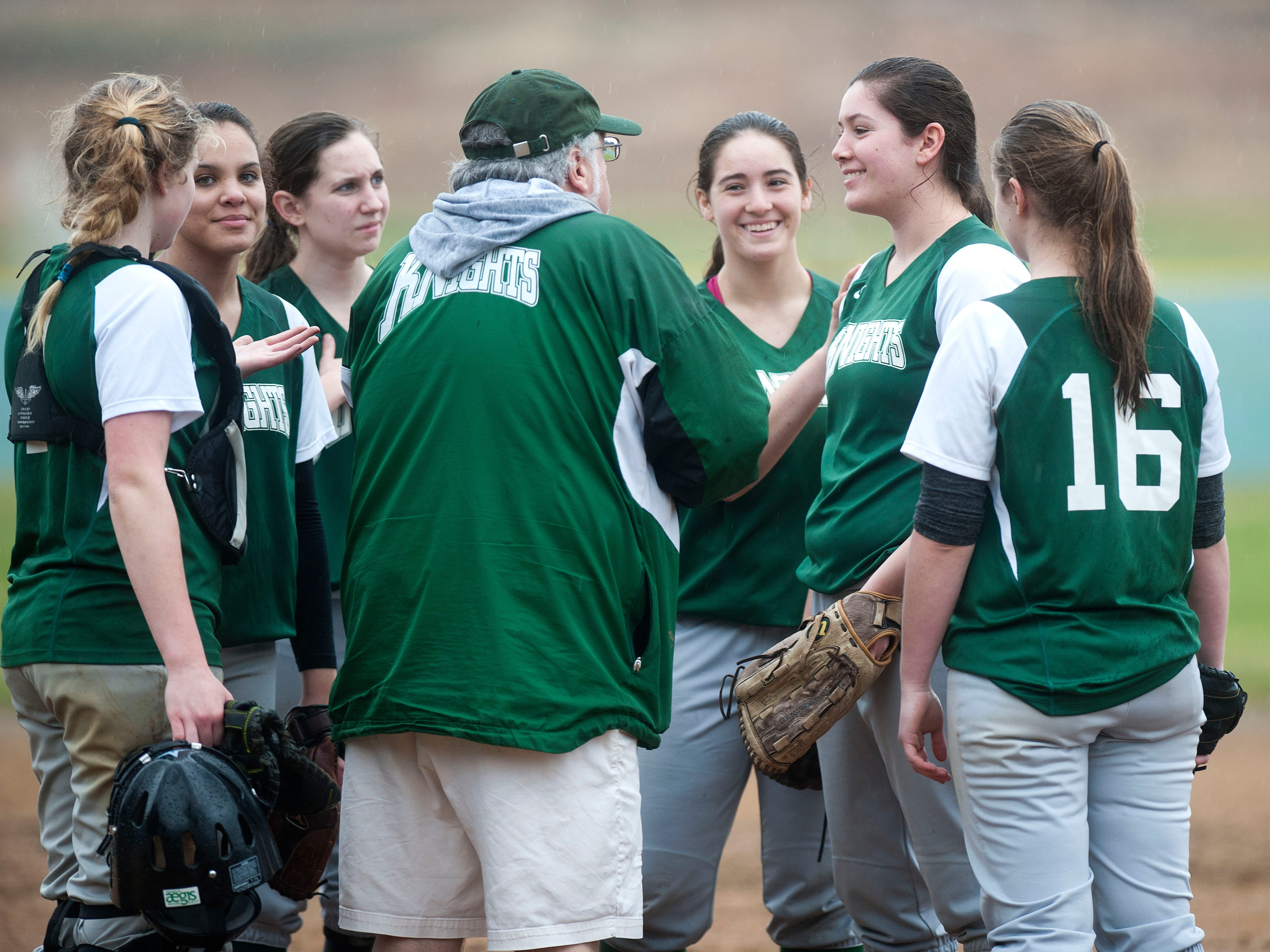 The Rice girls softball team meets on the mound between innings at Tuesday's game against Essex on April 22, 2014.