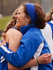 Croswell-Lexington assistant track and field and girls basketball coach Peggy Regan hugs one of her athletes.