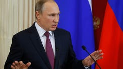 President Vladimir Putin gestures during a press conference