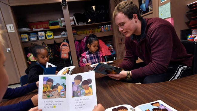 Noah Watson reads along with kindergartners during class at Reagan Elementary School April 28. Watson is a senior at Abilene High School, his father Scott is the class' teacher.