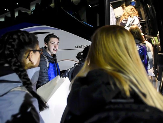 Students from local high schools board two buses at