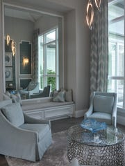 Overlooking the pool, the sitting room features a wall of mirrors that makes the room look twice its size.