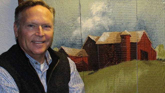 Chuck Law, seen next to a painting of a barn, will give a presentation on barn preservation as part of a Feb. 24 Door County Historical Society program on barns.