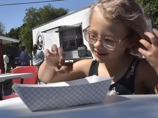 Eden Calkins of Algoma dining on picnic tables surrounding Skaliwags food truck.