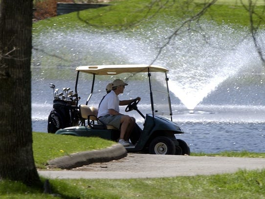 -  -Golfers drive their cart by the pond at Spook Rock