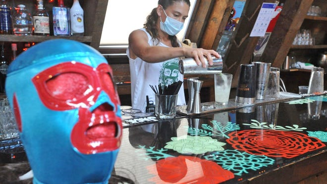 Lenny's Hideaway co-owner Stephanie Burke mixes a drink at their Cohasset restaurant's uniquely decorated bar,Thursday, July 9, 2020. Tom Gorman/For The Patriot Ledger