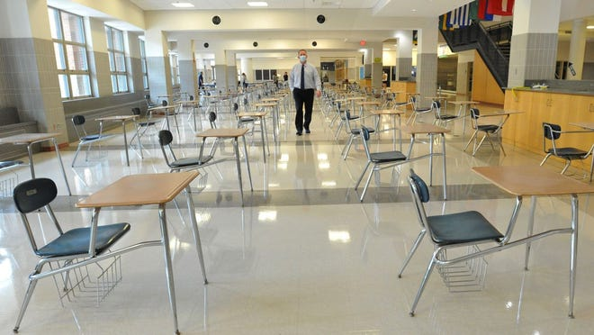 Executive Director of Career and Technical Education Keith Segalla walks between rows of socially distanced desks that replace tables and chairs in the Quincy High School cafeteria, Friday, Sept. 11, 2020. Tom Gorman/For The Patriot Ledger