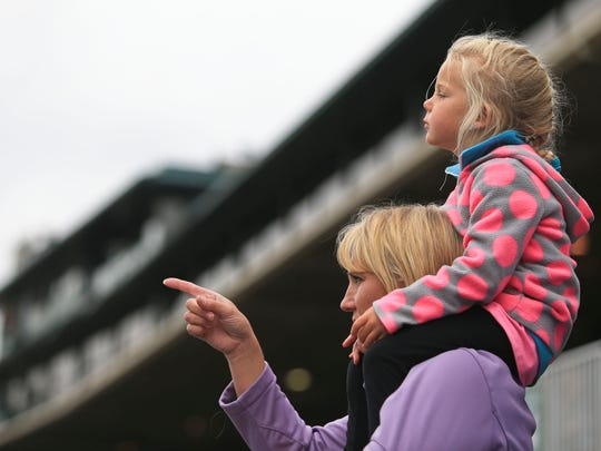 Erin Erquiaga has daughter Kara, 4, on her shoulders as the pair watch the start of the first race at Keeneland Friday.