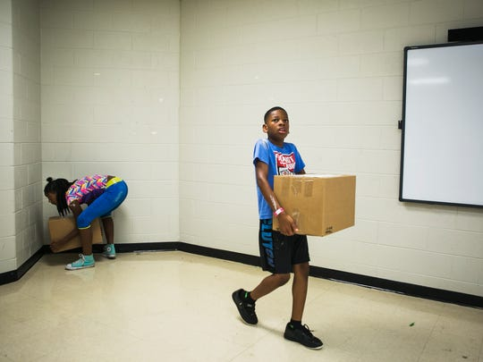 July 22, 2017 - Siblings Arianna Davis (left), 10, and Tyrone Davis II, 9, collect items from a classroom at Dexter Elementary during clean up day at the Cordova school on Saturday. Shelby County Schools invited the community to volunteer to help spruce up campuses before the arrival of the new year.