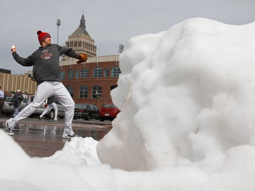 Red Wings pitcher Ryan Pressly, framed by a pile of melting snow, works out by throwing in the VIP Parking Lot during the Wings practice at snow covered Frontier Field in Rochester Tuesday, April 1, 2014.