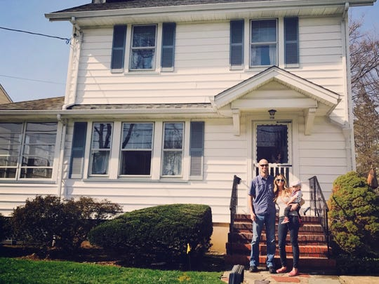 Ryan and Melissa Fahy with their son, Dex, stand in front of their New Jersey home.