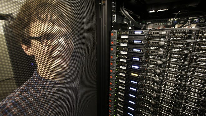 Massachusetts Institute of Technology researcher Carl Vondrick stands next to a computer server cluster on the Cambridge, Mass., campus. In a project that Vondrick led, a computer that binge-watched TV shows got better at predicting what the actors would do next.
