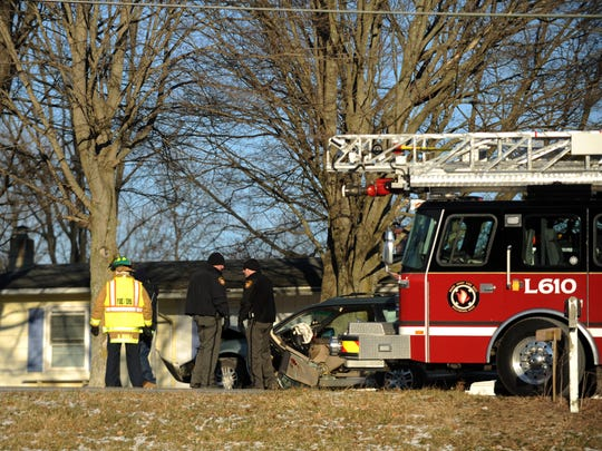Basil Joint Fire District firefighters and Fairfield County Sheriff's Deputies stand next to a car Thursday, Dec. 28, 2017, in Liberty Townsihp. The driver of a car was flown to Grant Medical Center in Columbus after driving head on into a tree on Basil Road north of Baltimore.