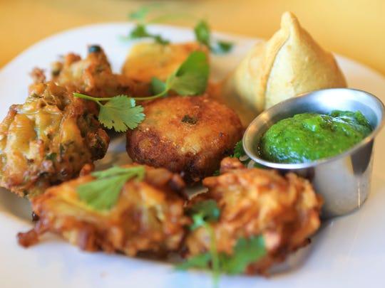 The vegetarian appetizer platter features veg samosa,