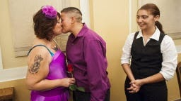 Jamie, left, and Bea Gallegos kiss after saying their vows while their adopted daughter Whitney Gomez, 15, stands near at the Pueblo County Courthouse in Pueblo, Colo.,
