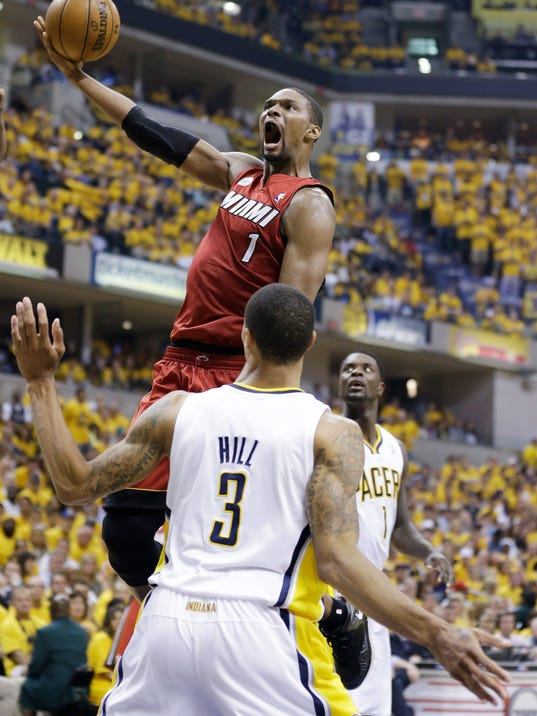 FILE - In this June 1, 2013 file photo, Miami Heat center Chris Bosh (1) goes up for a shot against Indiana Pacers guard George Hill (3) during the first half of Game 6 of the NBA Eastern Conference basketball finals in Indianapolis. Signing day has arrived in the NBA, if the biggest free agents care to grab their pens. But it's unclear if Carmelo Anthony, Chris Bosh and Dwyane Wade _ who all might be waiting on LeBron James to go first _ are ready. (AP Photo/Michael Conroy, File)