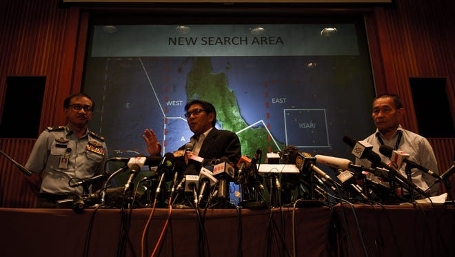 Director General of Civil Avition Department Azharuddin Abdul Rahman, center, explains to journalists the new search area as Malaysia Airlines Group CEO Ahmad Jauhari Yahya, right, and Malaysia Royal Air Force Maj. Gen. Afendi Buang listen.