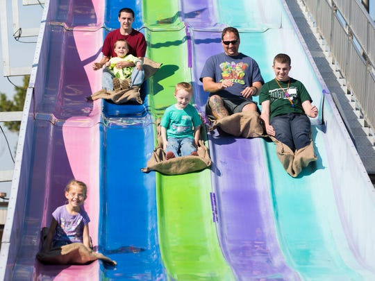 Kids and adults both enjoy going down the Fun Slide at Fall Fest during the Special Kids Day on Tuesday morning.