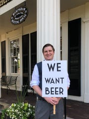 "Ryan Worbs, a former board member of the Licking County Historical Society, poses outside with the traditional ""We Want Beer"" sign brandished during prohibition times."