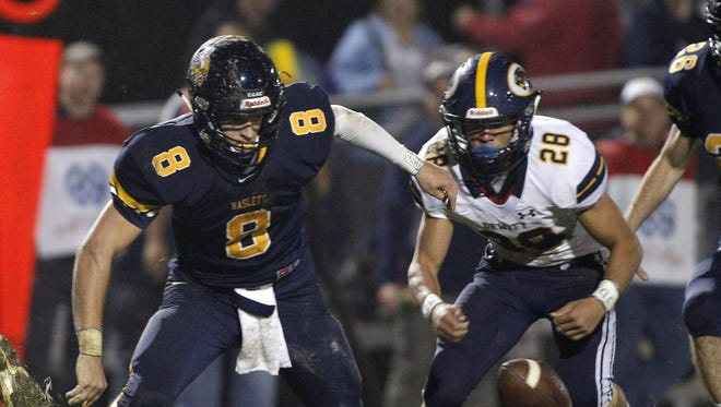 Haslett's Hyrum Tibbitts, left, and DeWitt's Quenten Hall (28) chase Tibbitts' fumble Friday, Oct. 6, 2017, in Haslett, Mich. The ball was recovered by DeWitt's Michael Wilkinson. DeWitt won 28-0.