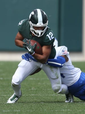 Michigan State's R.J. Shelton is tackled by Air Force's Kalon Baker during second half action on Saturday, September19, 2015 at Spartan Stadium in East Lansing Michigan.