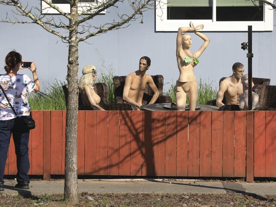 In this photo taken Monday, March 18, 2019, a woman stops to photograph a display of mannequins in Santa Rosa, Calif. Homeowner Jason Winduce set up the display, after a neighbor in the area complained to the city about his six-foot-tall fence. Winduce had to cut the fence to three feet. (Kent Porter/The Press Democrat via AP)