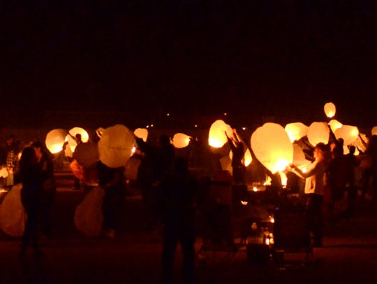 A crowd lights lanterns in preparation for mass ascension at a previous lantern festival in Fernley.