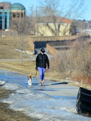 Mary Nezt walks along the River's Edge Trail with her dog Abby in January.