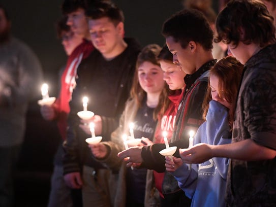 Friends of Roman Kellough attend a candlelight service