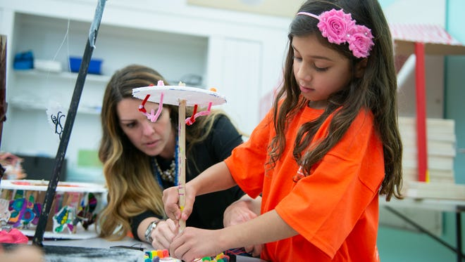 """Quinn Karaty, right, who said she is 6½, works on a STEM project, """"Making a Circus with Circuits"""" at George Washington Elementary School in Wyckoff. The project was made possible by a STEM Classroom Grant for the 2017-2018 school year from O&R. Lending  Quinn a hand is, at left, Wyckoff School District special projects supervisor Stacey Linzenbold."""