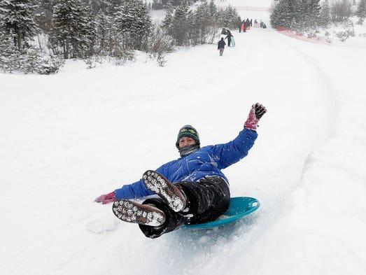 Patty Lang rides a snow disk down one of the runs at