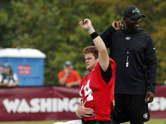 New York Jets head coach, Todd Bowles, right, watches quarterback Sam Darnold (14) warm up during the New York Jets Washington Redskins NFL football training camp in Richmond, Va., Monday, Aug. 13, 2018. (AP Photo/Steve Helber)
