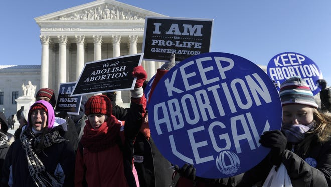 Pro-abortion and anti-abortion protesters rally outside the Supreme Court in Washington, Wednesday, Jan. 22, 2014. Thousands of abortion opponents faced wind chills in the single digits to rally and march on Capitol Hill to protest legalized abortion, with a signal of support from Pope Francis. (AP Photo/Susan Walsh)