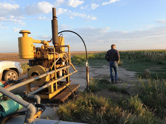 Farmer Jay Garetson looks at a cornfield next to a pump on his family's farm in southwestern Kansas.