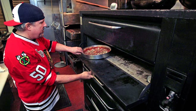 South of Chicago Pizza and Beef owner Bob Jaeger puts a deep dish pizza into the four-deck oven on Saturday, March 15, 2014 at the restaurant's newest location, 13578 E. 131st St. at Saxony in Fishers, which opened for business on January 31. Already Jaeger is talking about expanding his kitchen space in the building to make room for more ovens to keep up with demand. A third restaurant location is planned for Greenwood in 2015 (the first location is in Fletcher Place).
