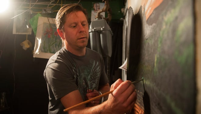 Painter Matthew Green works on a piece in the studio of his Oaklyn home.