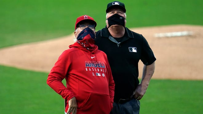 Umpire Bill Miller, seen here with Angels manager Joe Maddon during a game last month, is the crew chief for the 2020 World Series.
