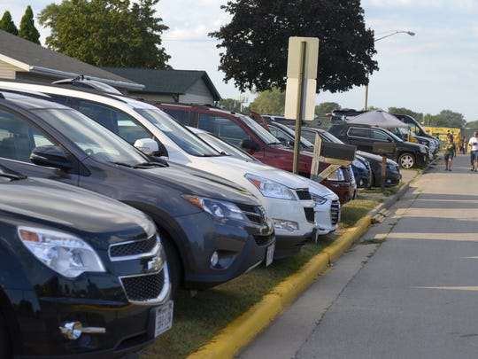 Cars line the front yards of houses near Lambeau Field during the preseason game against the Oakland Raiders, Aug. 18, 2016.