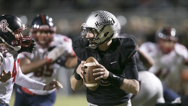 Hamilton High quarterback Travis Lockhart looks to pass against Centennial High during the first quarter of the high school football game at Hamilton High in Chandler on Friday, November 13, 2015.