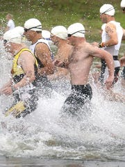 Competitors sprint into the lake at the start of the