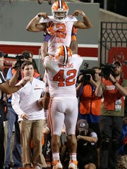 Clemson's Christian Wilkins (42) lifts quarterback Kelly Bryant (2) following Bryant's touchdown against North Carolina State during the second half of an NCAA college football game in Raleigh, N.C., Saturday, Nov. 4, 2017. Clemson won 38-31. (AP Photo/Gerry Broome)
