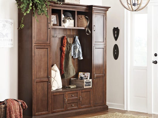 A cabinet serving as storage in the foyer of a home. One portion of an open foyer can function as a mudroom with help from a cabinet, like the one shown here, that combines closed storage, hanging space, shelving and seating.