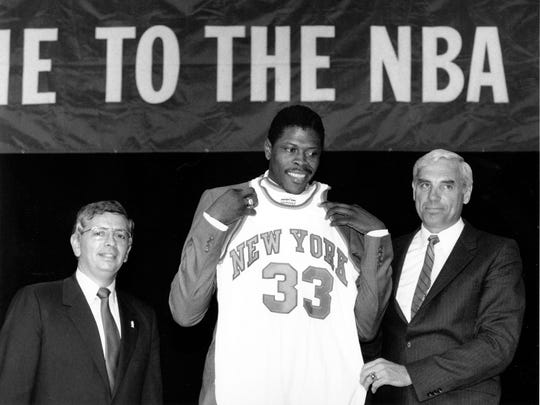 Patrick Ewing accepting his Knicks jersey from Dave DeBusschere, right, general manager of the Knicks, as NBA commissioner David Stern look on, at the 1985 NBA Draft in New York.