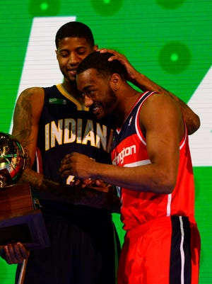John Wall celebrates with Toronto Raptors guard Terrence Ross and Indiana Pacers forward Paul George after the 2014 NBA All Star dunk contest.