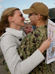 Breanna Squires embraces her husband, Harley, while 8-month-old daughter Olivia looks on after Harley disembarked the USS Bremerton at Naval Base Kitsap-Bremerton on Friday. The submarine made its final journey from Pearl Harbor to Puget Sound Naval Shipyard.