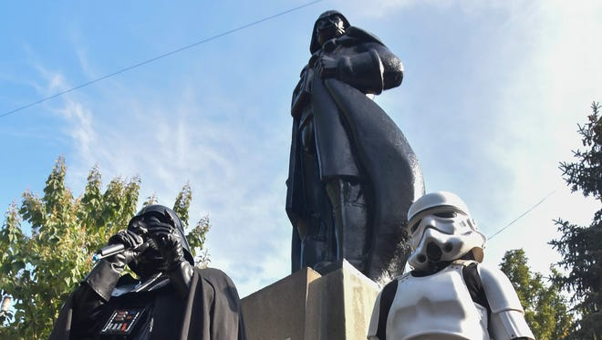 """A man dressed as the """"Star Wars"""" character Darth Vader speaks in front of the Darth Vader monument in Odessa, Ukraine, Friday Oct. 23, 2015. The monument was built on the base of a former statue of Soviet Union founder Vladimir Lenin, which was demounted earlier. Candidate Darth Vader (and yes, that's his legal name) is running for city mayor of Odessa in local elections Sunday, Oct. 25."""