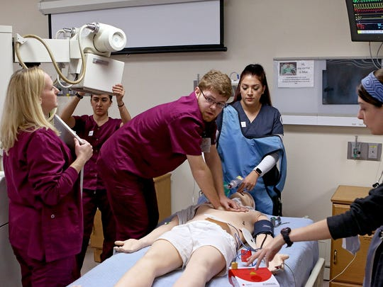 Devin Helsel, radiology major at Midwestern State University, center, performs CPR as a team of nursing, radiology and respiratory care students work through a scenario Friday morning in Bridwell Hall.